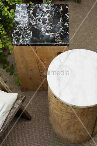 Marmorplatten auf Holzklötzen als Beistelltische im Garten
