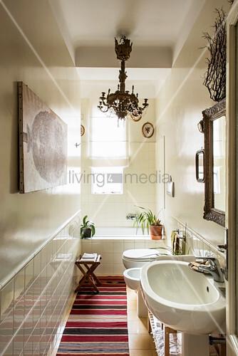 Chandelier and bathtub in niche in narrow L-shaped bathroom