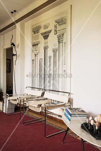 Architectural diagram of columns on wall above designer chairs