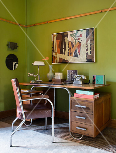 Old wooden desk with metal frame against green wall