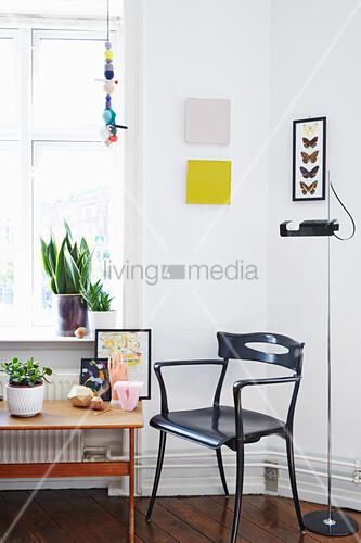 Schwarzer Stuhl neben einem niedrigen Tisch mit Dekoaccessoires