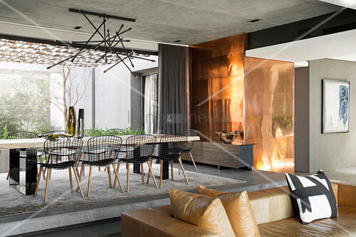 Long dining table and metal-clad wall in luxurious interior