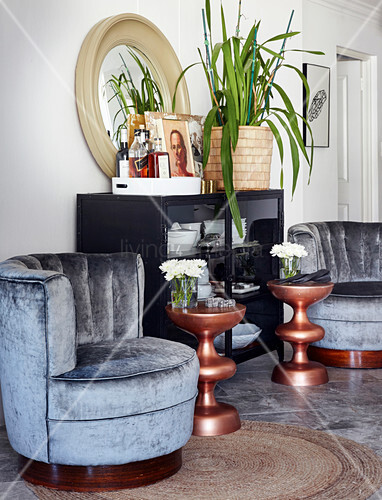 Two velvet easy chairs and copper-coloured side tables next to display cabinet