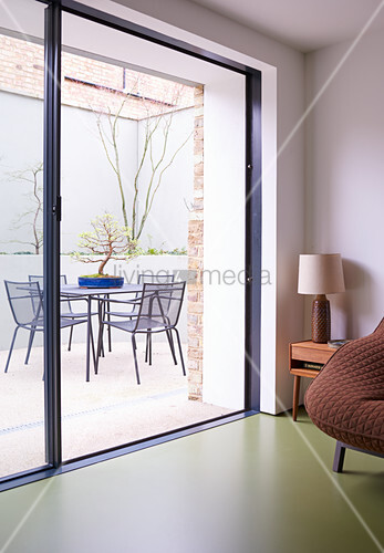 View of bonsai tree on table and chairs through open terrace doors