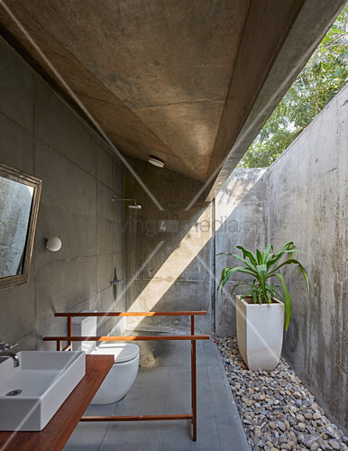 Modern bathroom made from rough concrete in architect-designed house