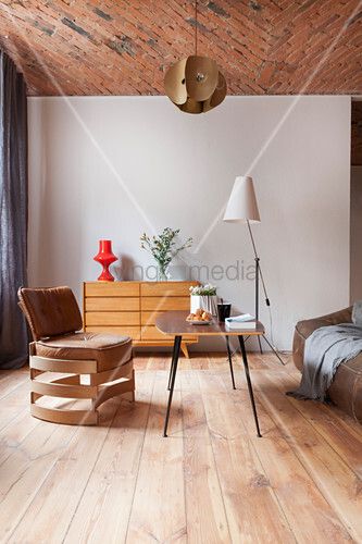 Designer leather chair, coffee table and sideboard in open-plan interior with brick ceiling