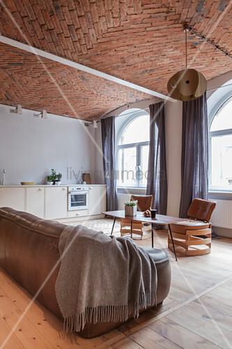 Ledersofa, Coffeetable und Designer-Lederstühle in offenem Wohnzimmer mit Ziegeldecke, im Hintergrund Küchenzeile