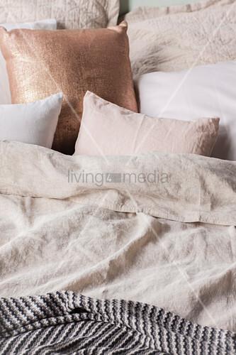 Kissen in Champagnerfarben auf dem Bett mit Leinenbettwäsche