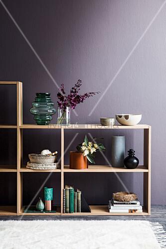 Offenes Holzregal mit Dekoaccessoires vor violetter Wand