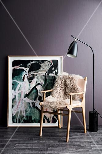 Skandinavischer Stuhl mit Schaffell vor Gemälde und violetter Wand