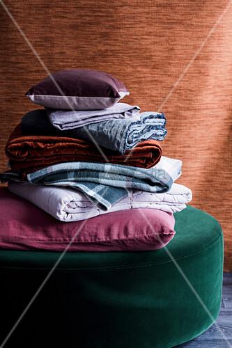 Ein Stapel aus Kissen und Decken auf einem grünen Samthocker