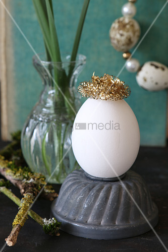 Egg with gild metal crown on old cake tin