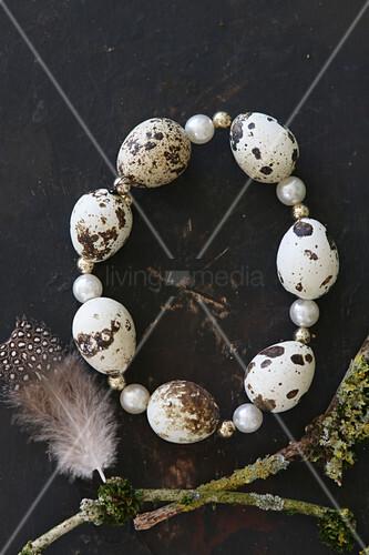 Kranz aus aufgefädelten Wachteleiern und Perlen auf schwarzem Grund