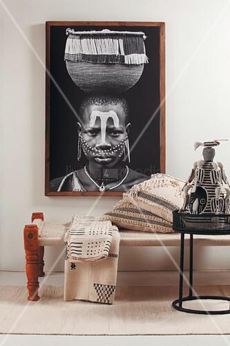 Bild einer afrikanischen Frau mit Korb über einer Liege mit Ethnoaccessoires