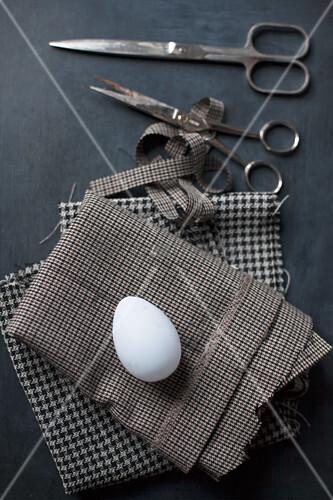 Weißes Ei auf kariertem Stoff