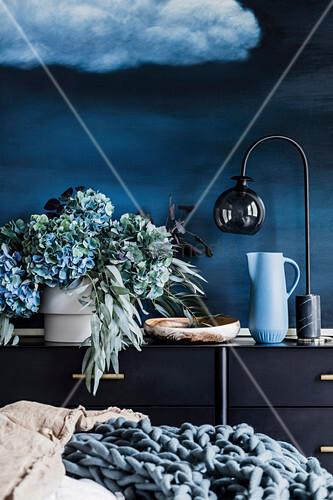 Vase mit Hortensien und Eucalyptuszweigen, Schale, Krug un Tischlampe auf Sideboard vor blauer Wand