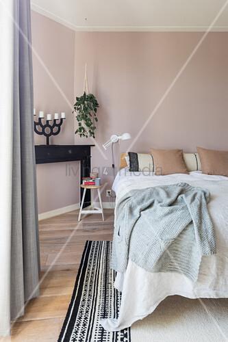 Doppelbett, Pflanzenampel und Kaminkonsole mit Kerzenhalter im Schlafzimmer