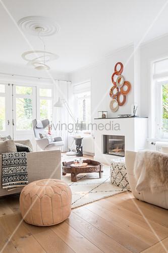 Helle Polstermöbel, marokkanischer Sitzpouf, Mühlstein-Tisch und Kamin im Wohnzimmer