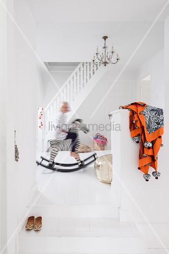 Kind auf Schaukelpferd in weißem Treppenhaus