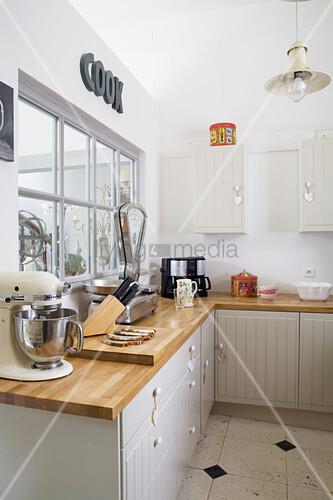 Landhausküche in Grautönen mit Holzarbeitsplatte und Innenfenster