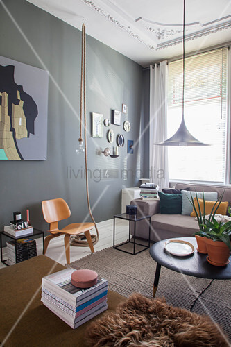 Sofa, coffee table and chair in living room of period apartment with dark wall