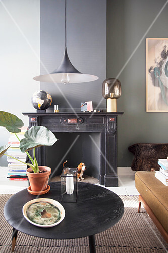 Black coffee table and disused fireplace in living room of period apartment with dark wall