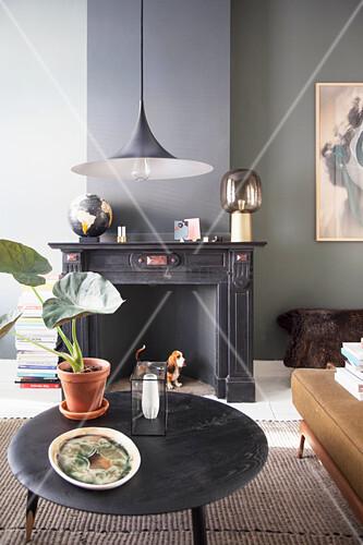 Schwarzer Couchtisch und stillgelegter Kamin im Altbau-Wohnzimmer mit dunkler Wand