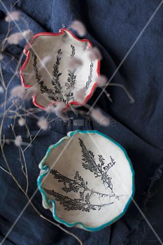 Schalen aus Ton mit eingeprägtem Blumenmotiv und bemaltem Rand