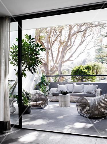 Designer-Korbmöbel und Grünpflanzen auf Balkon