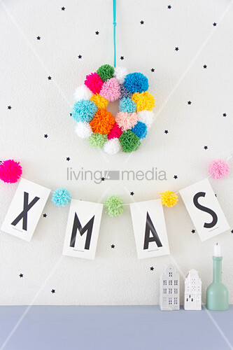 Wreath of colourful pompoms above Xmas garland
