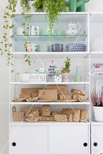 Advent calendar of brown parcels on white shelves