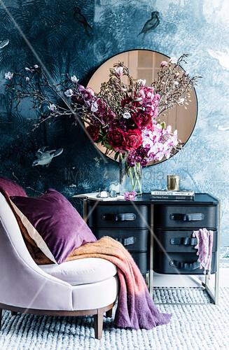 Pastellfarbener Polstersessel mit Plaid und Kissen vor Kommode mit üppigem Blumenstrauss