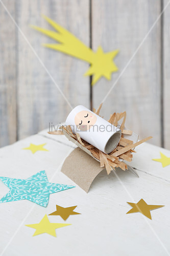 Baby in manger handmade from cardboard tubes
