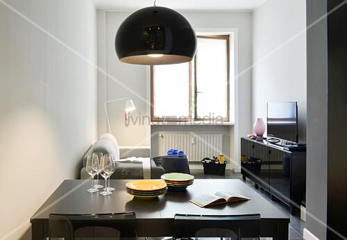 Blick über den Esstisch ins kleine Wohnzimmer mit offenem Fenster