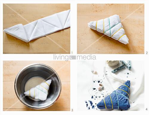 Tischdecke mit Shibori-Technik färben, hier: Stoff falten, mit Gummiband fixieren und Wässern