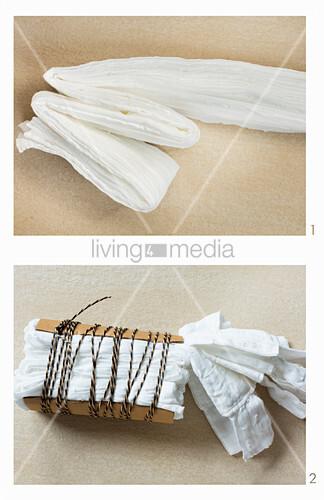 Vorbereitung: Vorhang mit Shibori-Technik färben, hier: Stoff falten, mit dicker Pappe fixieren und mit Band umwickeln