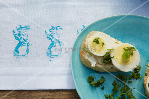 Baguette with sliced egg on Easter-themed tablecloth with rabbit motif