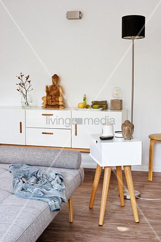 Moderner Beistelltisch mit Schublade neben grauem Tagesbett