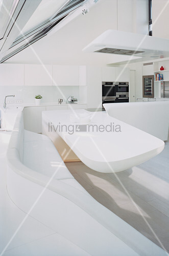 Dining table and curved corner bench in futuristic kitchen-dining room