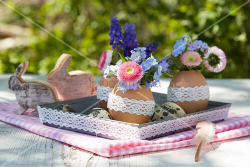 Blumensträusschen in ausgeblasenen Eiern mit Spitenborte als österliche Tischdekoration