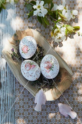 Kunstvoll bemalte Ostereier auf Kresse in Holzschale