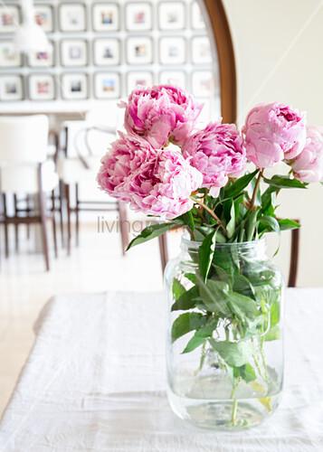 Peonies in glass vase