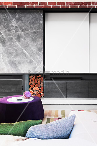 Polsterhocker vor Wohnzimmerwand mit Kamin, Holzlager und Schiebeelement
