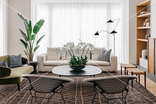 Retro Sitzmöbel und Couchtisch auf braun gemustertem Teppich vor Terrassentür mit bodenlangem Vorhang