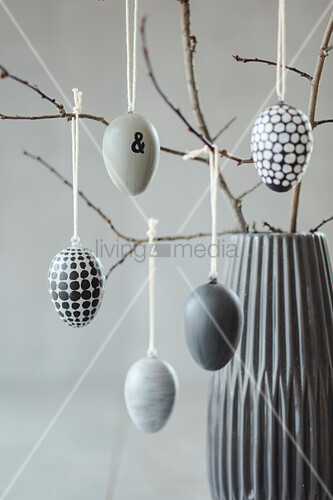 Easter eggs hand-painted in shades of grey hanging from twigs