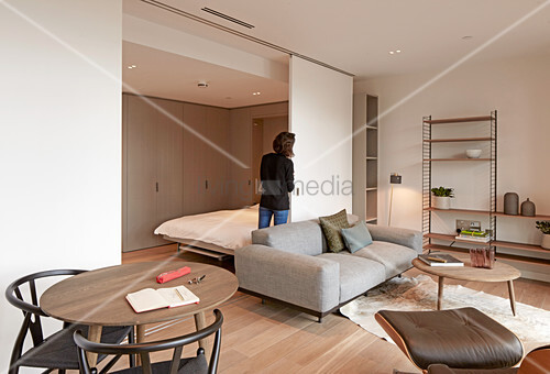 Woman moving flexible partition wall in studio apartment
