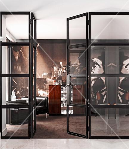 Blick durch Glastür in Hausbar mit Bartheke, Ledersesseln und Desinger-Tapete