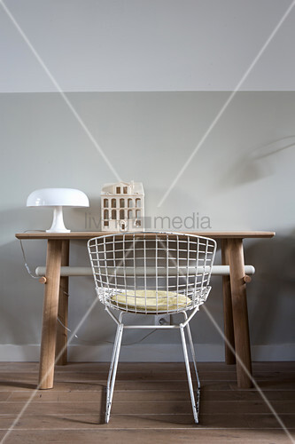 Table lamp and ceramic house on desk and classic chair in front of pale grey wall