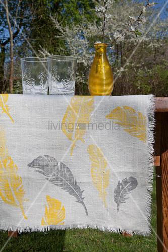 Mit gelben und grauen Federn bedruckter Tischläufer