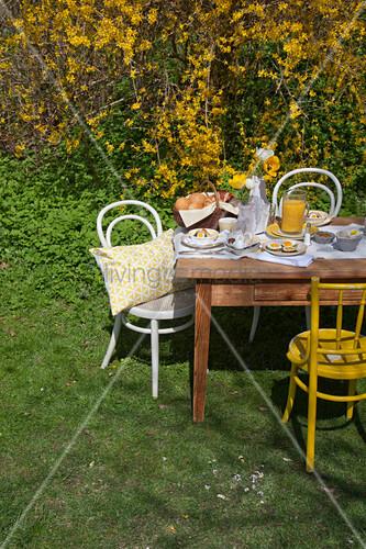 Fürs Osterfrühstück gedeckter Tisch im Garten